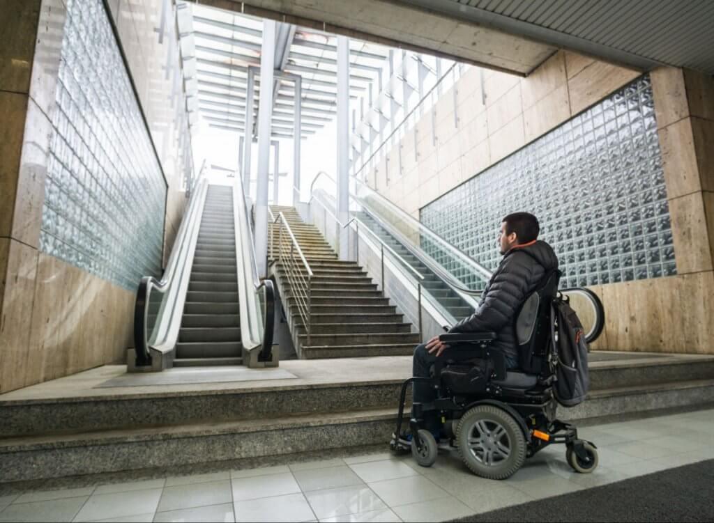 Які інклюзивні новинки впроваджує столичний метрополітен (ВІДЕО). київ, доступність, комфорт, метрополітен, інвалідність, person, clothing, stairs, footwear, station. A person sitting on a bench in front of a building