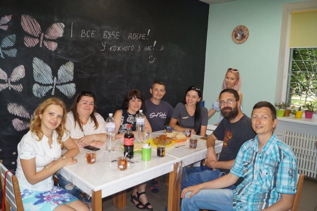 До Тернополя приїхав американець з аутизмом, щоб передати власний досвід (ФОТО). біл петерс, тернопіль, аутизм, діагноз, інвалідність, person, table, wall, indoor, group, people, bottle, posing, clothing, drink. A group of people sitting at a dinner table posing for the camera