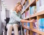 Які професії вже здобули цьогоріч мешканці Кіровоградщини з інвалідністю?. кіровоградщина, професія, підприємство, служба зайнятості, інвалідність, person, book, bookcase, girl, shelf, sitting, furniture, woman, indoor, library. A woman sitting next to a book shelf
