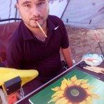 Світлина. Федір Романов пише картини, тримаючи пензлик зубами. Життя і особистості, інвалідність, художник, картина, Федір Романов, артрогипоз