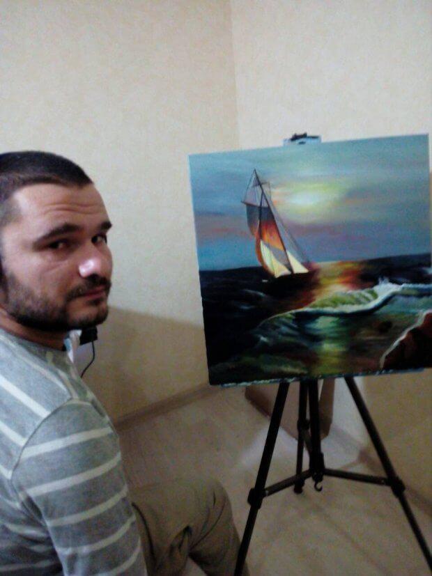 Федір Романов пише картини, тримаючи пензлик зубами. федір романов, артрогипоз, картина, художник, інвалідність